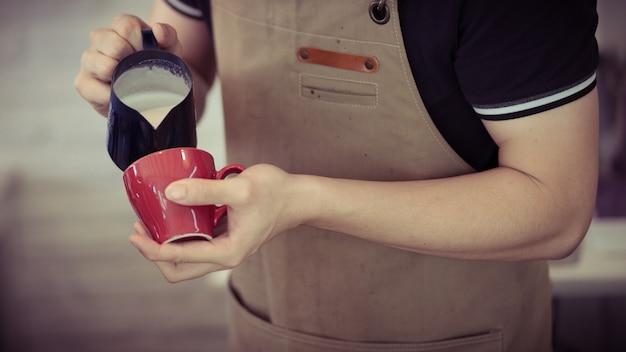 Profesjonalny Barista Nalewający Płynne Mleko, Aby Zrobić Latte Art W Czerwonej Filiżance Gorącej Kawy, Retro Ton Premium Zdjęcia