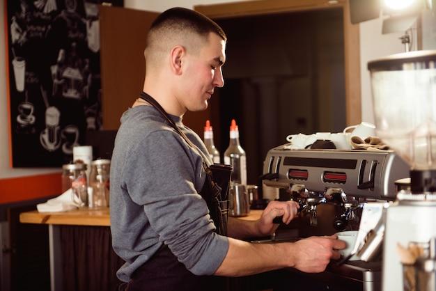 Profesjonalny barista trzymając metalowy dzbanek rozgrzewający mleko za pomocą ekspresu do kawy. Premium Zdjęcia