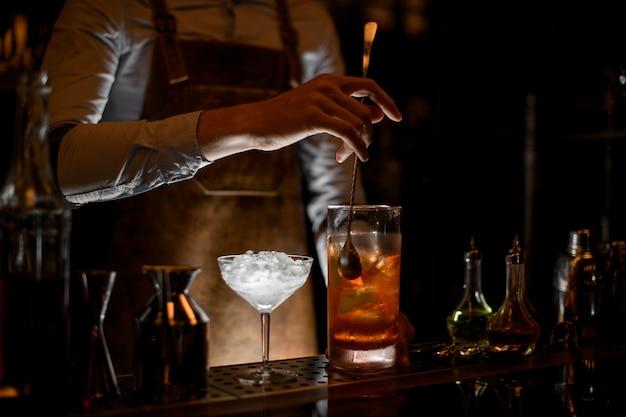 Profesjonalny Barman Mieszający Koktajl W Szklanej Miarce Premium Zdjęcia