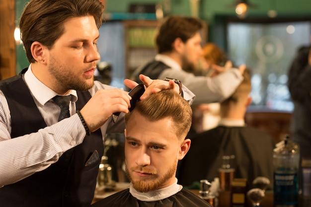 Profesjonalny fryzjer pracujący w swoim zakładzie fryzjerskim Premium Zdjęcia