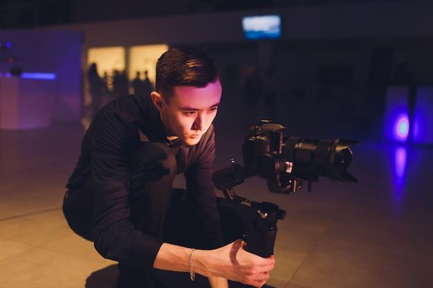 Profesjonalny Kamerzysta Trzymający Kamerę Na 3-osiowym Gimbalu. Kamerzysta Używa Steadicamu. Profesjonalne Urządzenia Pomagają Tworzyć Wysokiej Jakości Filmy Bez Wstrząsania. Premium Zdjęcia