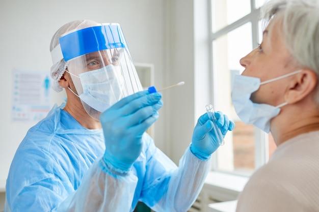 Profesjonalny Pracownik Medyczny Noszący Osobiste Wyposażenie Ochronne, Testujący Starszą Kobietę Pod Kątem Niebezpiecznej Choroby Za Pomocą Testera Premium Zdjęcia