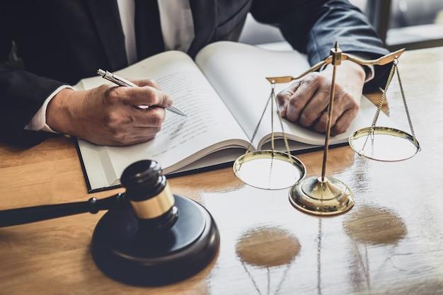 Profesjonalny prawnik płci męskiej lub sędzia pracujący z dokumentami kontraktowymi, dokumentami i młotkiem i skalą sprawiedliwości na stole w koncepcji sali sądowej, prawa i usług prawnych Premium Zdjęcia