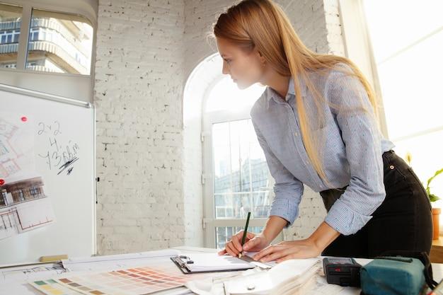 Profesjonalny Projektant Wnętrz Lub Architekt Pracujący Z Paletą Kolorów, Rysunkami Pomieszczeń W Nowoczesnym Biurze. Darmowe Zdjęcia
