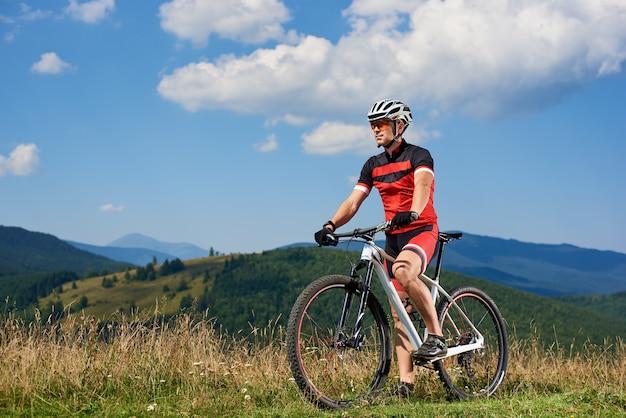 Profesjonalny rowerzysta w odzieży sportowej i kasku na rowerze górskim Premium Zdjęcia