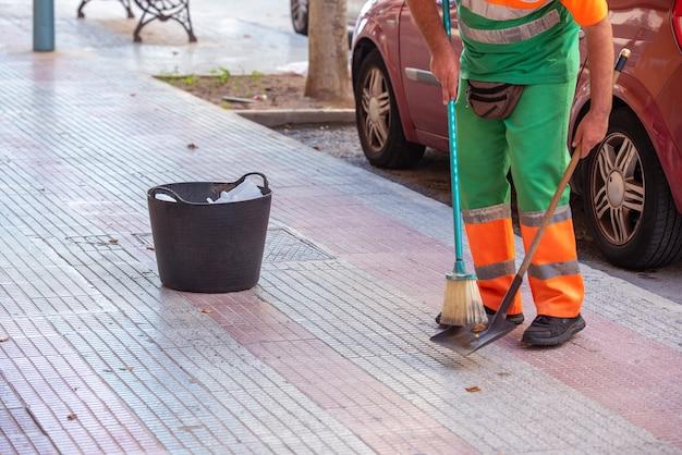 Profesjonalny Sprzątacz Zamiatający Ulice Miasta, Z Koszem Do Wyrzucania Zbieranych śmieci Premium Zdjęcia