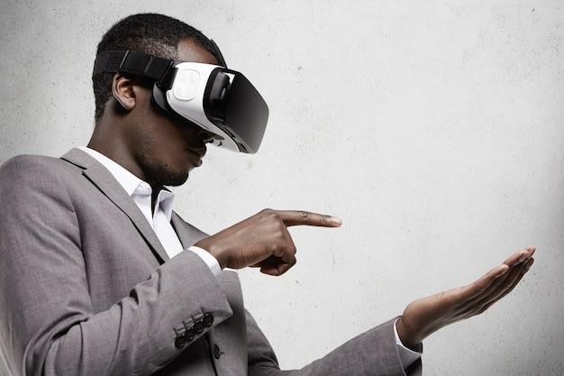 Profil Afrykańskiego Biznesmena W Szarym Garniturze, Noszącego Okulary 3d Z Zestawem Słuchawkowym W Biurze, Gestykulującego, Jakby Trzymał Jakiś Gadżet Na Dłoni I Dotykając Go Palcem Wskazującym Podczas Grania W Gry Wideo Darmowe Zdjęcia