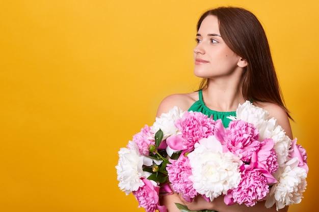 Profil Brunetki Młodej Damy W Zielonej Odzieży, Obejmującej Ogromny Bukiet Piwonii Darmowe Zdjęcia