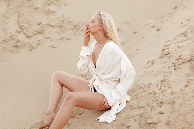 Profil Portret Seksownej Młodej Kobiety Blondynka W Białej Dużej Koszuli, Paląc Siedząc Na Piasku. Portret Na Zewnątrz. Premium Zdjęcia