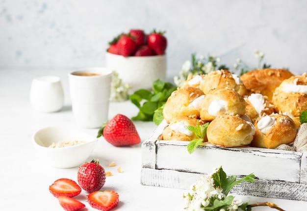 Profiteroles (choux à La Crème) - Francuskie Kulki Z Ciasta Francuskiego Z Twarogiem I śmietaną Z Truskawkami, Miętą I Filiżanką Kawy. Premium Zdjęcia