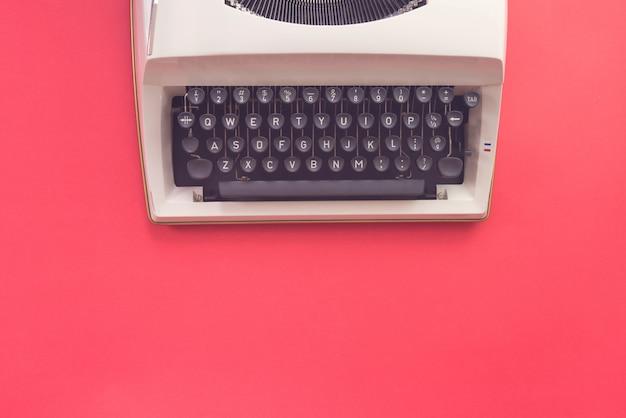 Projekt flay maszyny do pisania na czerwonym tle. styl retro. Premium Zdjęcia