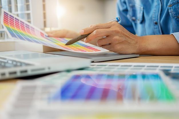 Projekt graficzny i próbki kolorów i pióra na biurku. Premium Zdjęcia