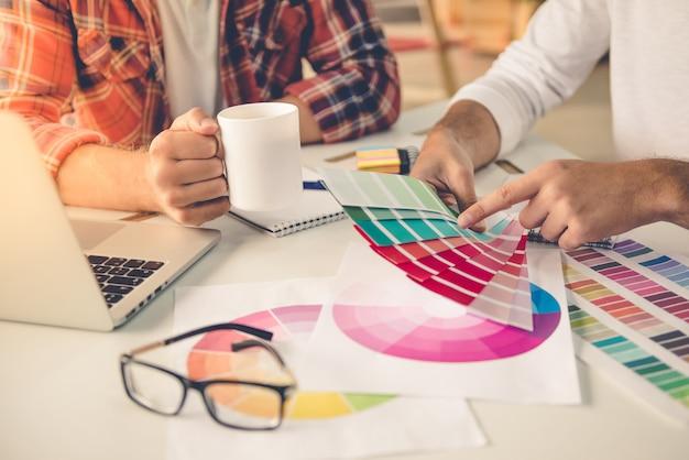 Projektanci w codziennych ubraniach omawiających kolory. Premium Zdjęcia