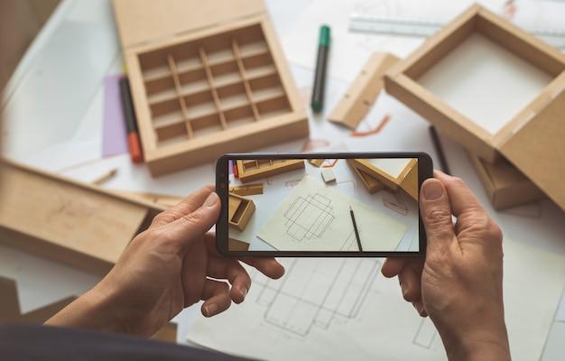 Projektant Opakowań Kartonowych Robi Zdjęcia Szkiców Projektu Na Blogu Na Smartfony. Premium Zdjęcia