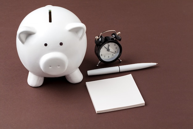 Prosiątko bank save monetę, budzika, czasu i pieniądze pojęcie. Premium Zdjęcia