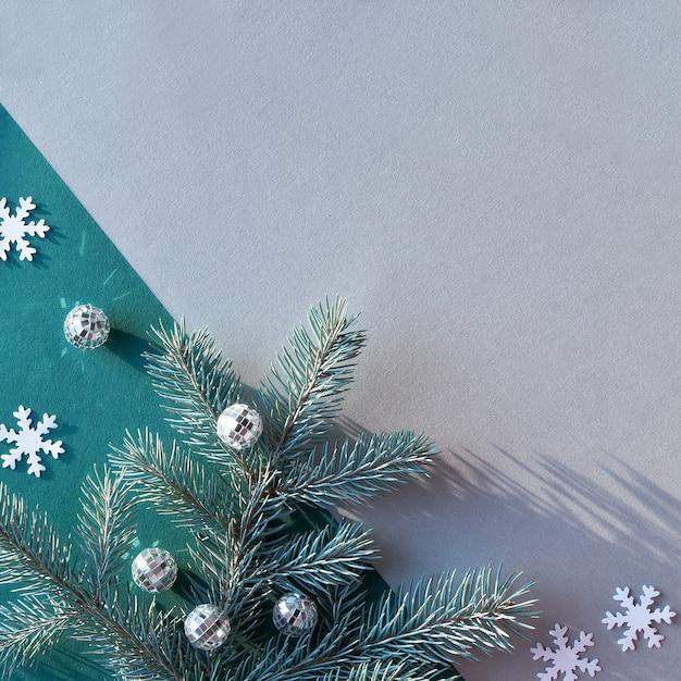 Proste Dekoracyjne Zimowe Tło Z Kopiowaniem Przestrzeni. Gałązki Jodły Na Dwukolorowym Zielono-szarym Papierze. Premium Zdjęcia