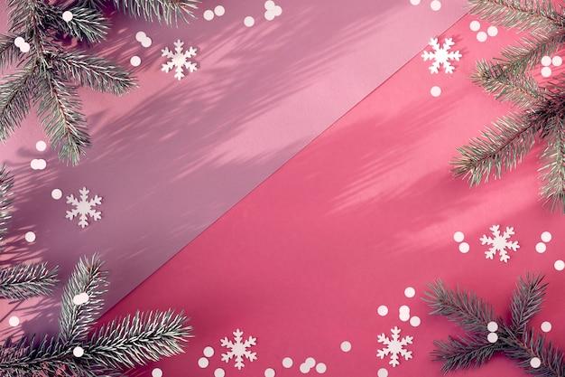 Proste Zimowe Tło. Gałązki Jodły Na Dwukolorowym Różowym Papierze Z Konfetti. Premium Zdjęcia