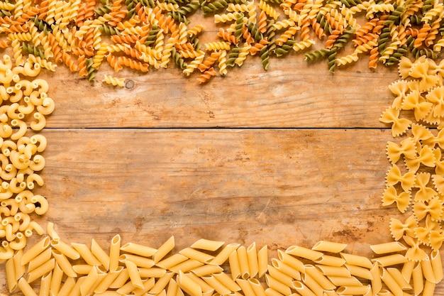 Prostokątna rama wykonana z różnych rodzajów surowego makaronu na drewnianym stole Darmowe Zdjęcia