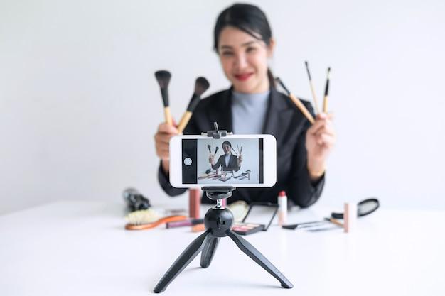 Prowadząc Działalność Online W Mediach Społecznościowych, Piękna Kobieta Blogerka Prezentuje Obecny Samouczek Kosmetyczny I Transmituje Na żywo Wideo Do Sieci Społecznościowej Podczas Nagrywania Nauczania Premium Zdjęcia