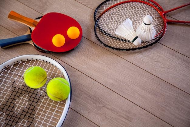 Przedmioty do fitnessu, rakiet i akcesoriów do badmintona, tenisa stołowego i tenisa na tle drewna Premium Zdjęcia