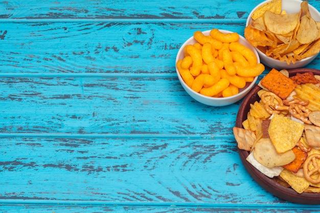 Przekąski do piwa, takie jak krakersy, frytki, ciastka na drewnianej powierzchni Premium Zdjęcia
