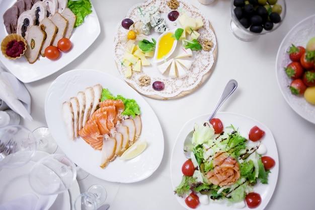 Przekąski różne rodzaje sera, salami i szynki. zdobiony stół, bufet Premium Zdjęcia