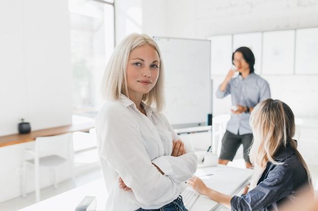 Przekonana Blondynka W Bluzce Stojącej Z Rękami Skrzyżowanymi W Biurze Z Dużym Flipchartem Darmowe Zdjęcia
