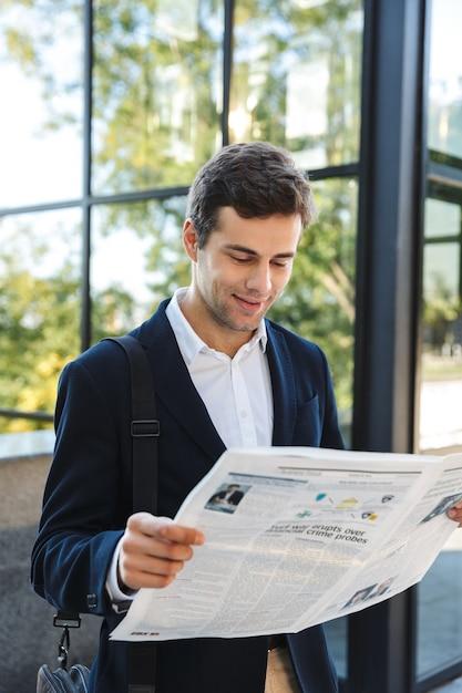 Przekonany, Biznesmen Czytanie Gazety Stojąc Na Zewnątrz Premium Zdjęcia