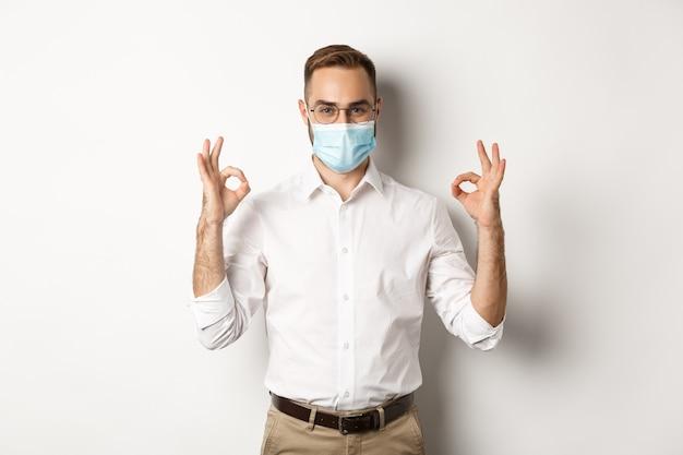 Przekonany, Biznesmen Noszący Maskę Medyczną I Pokazujący Dobre Znaki W Zatwierdzeniu, Białe Tło. Darmowe Zdjęcia