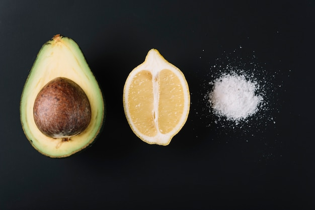 Przekrawający awokado i cytryny blisko soli na czerni powierzchni Darmowe Zdjęcia