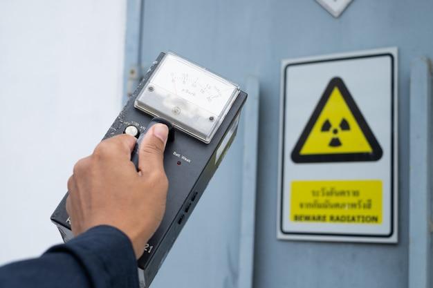 Przełożony za pomocą miernika pomiarowego sprawdza poziom promieniowania w strefie radioaktywnej Premium Zdjęcia