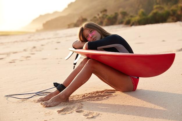 Przemyślana Kaukaska Kobieta W Kostiumie Kąpielowym, Używa Smyczy Do Surfowania Na Longboardzie, Pochyla Się Za Ręce Darmowe Zdjęcia
