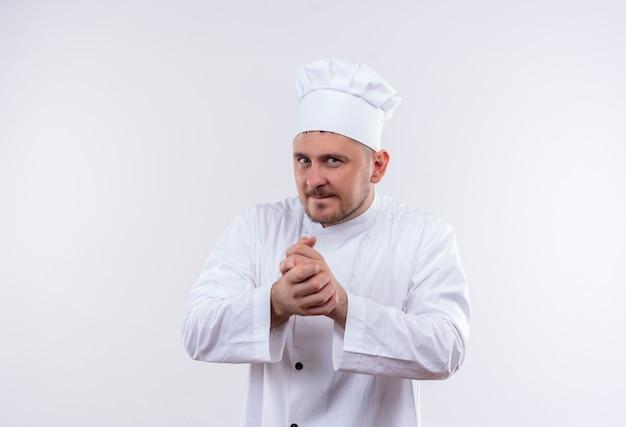 Przemyślany Młody Przystojny Kucharz W Mundurze Szefa Kuchni, Trzymając Ręce Razem Na Odosobnionej Białej Przestrzeni Darmowe Zdjęcia