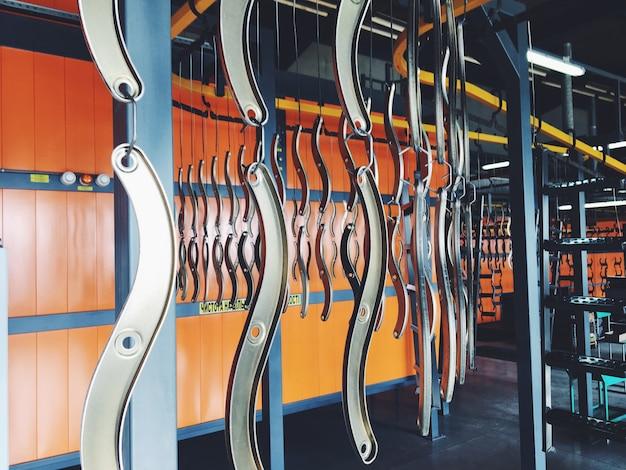 Przemysłowa linia przenośników w fabryce części metalowych. obróbka powierzchni części i malowanie części farbą proszkową. Premium Zdjęcia
