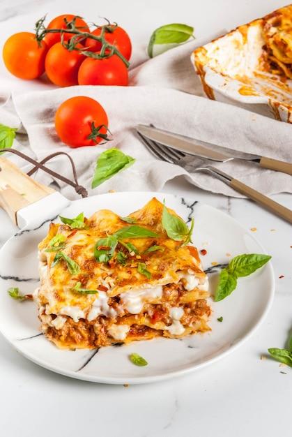 Przepis Na Włoskie Jedzenie. Kolacja Z Klasyczną Lasagne Bolognese Z Sosem Beszamelowym, Parmezanem, Bazylią I Pomidorami, Na Białym Marmurowym Stole, Premium Zdjęcia