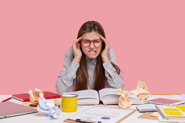 Przepracowana ładna Kobieta Gryzie Dolną Wargę, Cierpi Na Ból Głowy, Czyta Artykuł Naukowy W Książce, Ma Bałagan Na Stole Darmowe Zdjęcia