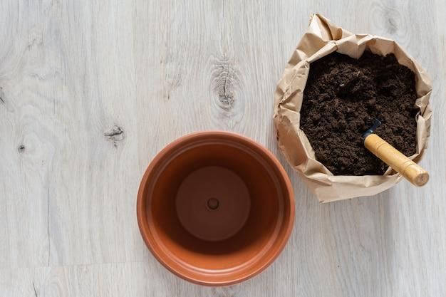 Przesadzanie Kwiatów W Nowej Brązowej Glinianej Doniczce, Przeszczep Rośliny Doniczkowej W Domu Premium Zdjęcia
