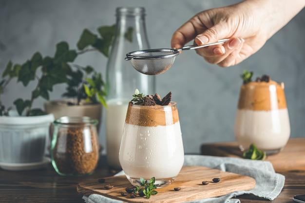Przesiewanie Proszku Kakaowego Przez Sito Nad Szklanką Mrożonego Pieniącego Się Napoju Dalgona Coffee Premium Zdjęcia