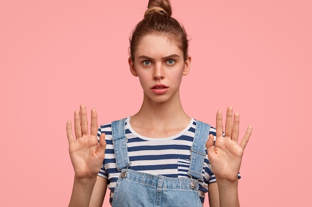 Przestań Panikować, Proszę! Urocza Poważna Niebieskooka Modelka Pokazuje Znak Stopu, Trzyma Dłonie Z Przodu Darmowe Zdjęcia