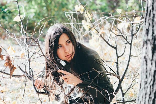 Przestraszona dziewczyna jest sama w lesie, chowa się wśród żółtych liści jesienią. Premium Zdjęcia