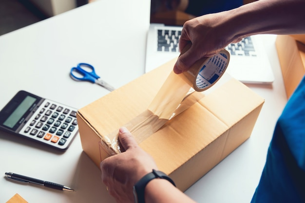 Przesyłka Sprzedaż Online. Obsługuje Dostawę Pracownika I Działa Pakowanie, Właściciel Firmy Sprawdza Zamówienie W Celu Potwierdzenia Przed Wysłaniem Klienta Pocztą Premium Zdjęcia