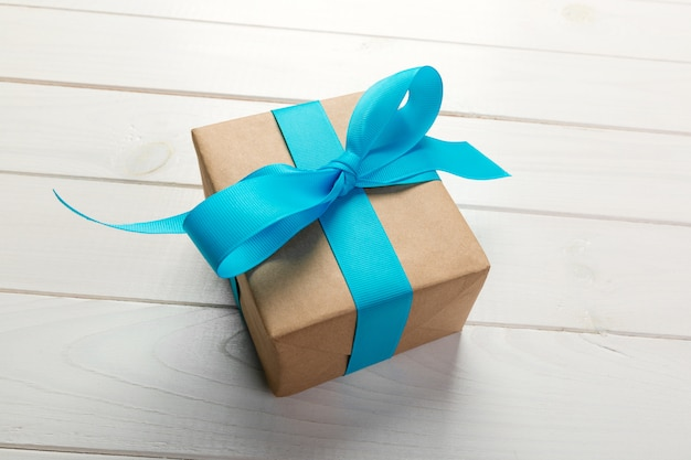 Przetwarzający papierowy prezenta pudełko z błękitnym faborkiem na starym drewnianym białym tle odgórny widok Premium Zdjęcia