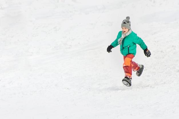 Przez śnieg biegnie chłopiec w zielonej kurtce i czerwonych spodniach. Premium Zdjęcia