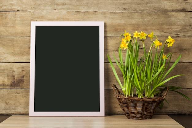 Przezroczysta Tablica I Wazon Z Wiosennymi Kwiatami Na Drewnianej Powierzchni. Koncepcja Początku Wiosny, Wakacji. Skopiuj Miejsce Premium Zdjęcia