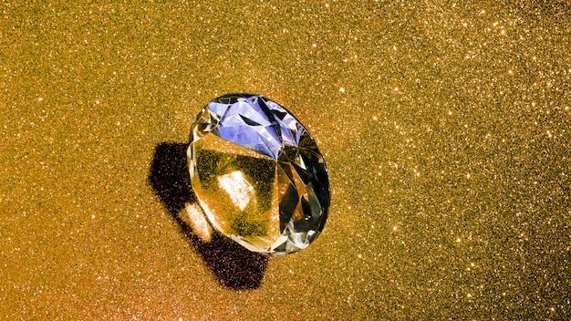 Przezroczysty błyszczący diament na tle złotym brokatem Darmowe Zdjęcia