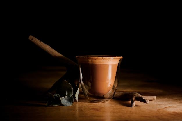 Przezroczysty kubek wypełniony gorącym i aromatycznym napojem kawowym z mlekiem Premium Zdjęcia