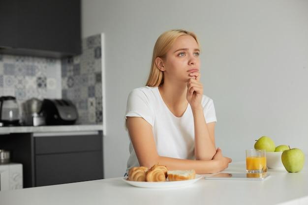 Przy Kuchennym Stole Siedzi Młoda Blondynka, Smutna, Patrzy W Zamyśleniu W Stronę Okna Darmowe Zdjęcia
