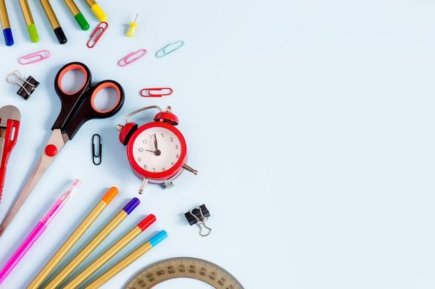 Przybory szkolne na niebieskim tle z copyspace dla projektu. ołówki, nożyczki, notatnik, budzik, widok z góry. powrót do szkoły Premium Zdjęcia