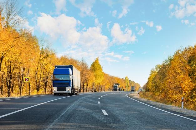 Przybywająca błękitna ciężarówka na drodze w wiejskim krajobrazie przy zmierzch jesienią Premium Zdjęcia
