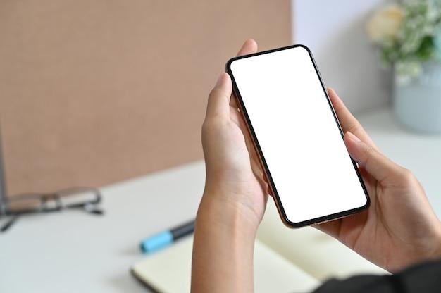 Przycięta strzał kobieta używa mockup smartphone na biurowym biurku Premium Zdjęcia